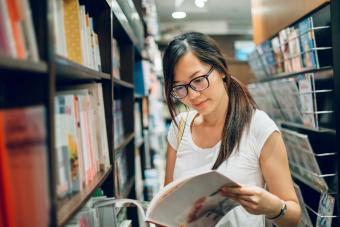 young lady reading book in bookstore