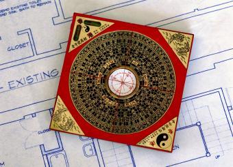 feng shui compass sitting on blueprints