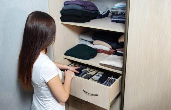 Girl organizing clothes in wardrobe