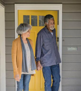 Senior couple leaving house and closing door