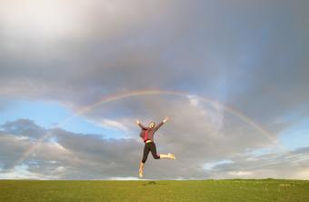 woman jumping in air celebrating feng shui good luck underneath a rainbos in the sky