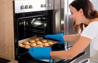 Woman placing tray in oven