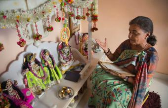 woman reciting prayers during pooja