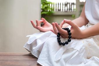 Black beads bracelet in girl hand while meditating