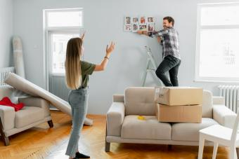 Man hanging family photo in living room