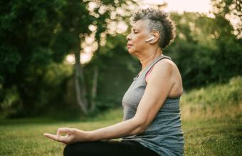 woman meditating while wearing earbuds