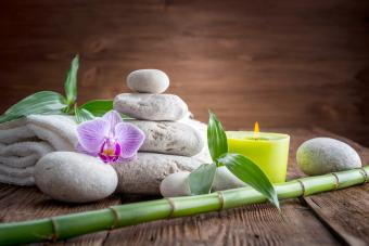 White Zen balance stones, an Orchid flower, a bamboo plant and a candle on a wooden table