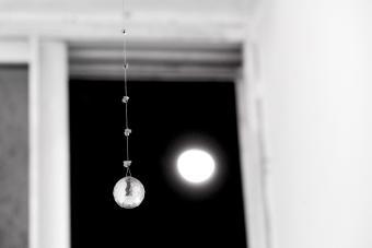 Crystal Ball On Ceiling Against Full Moon Seen Through Window