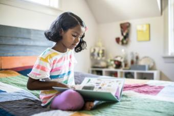 Girl reading book on her bed