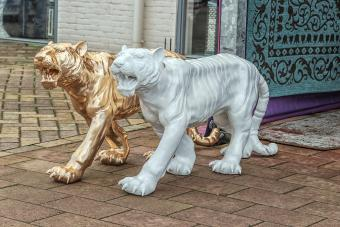 golden and white stone tigers on the street
