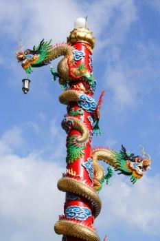 Chinese dragons coil up a pole.