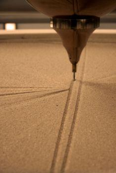 Pendulum on stand creates patterns in sand.
