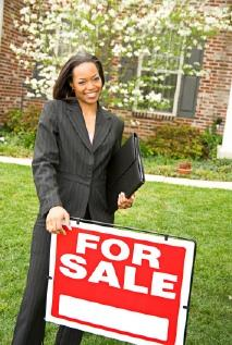 Realtor standing by for sale sign