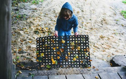 Boy holding walk-off door mat