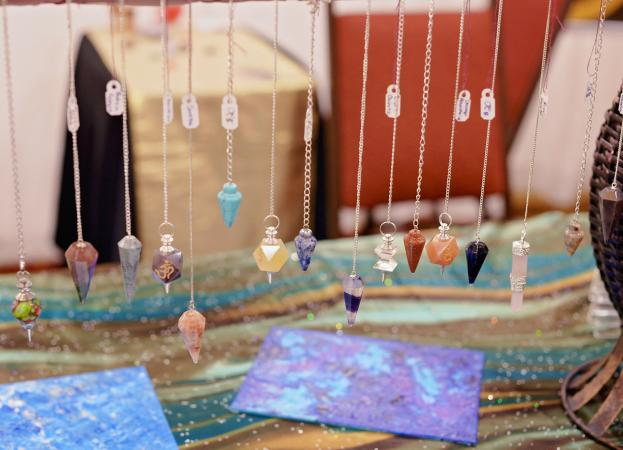 gemstone pendulums hanging on display