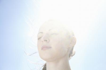 Meditating woman backlit by sun