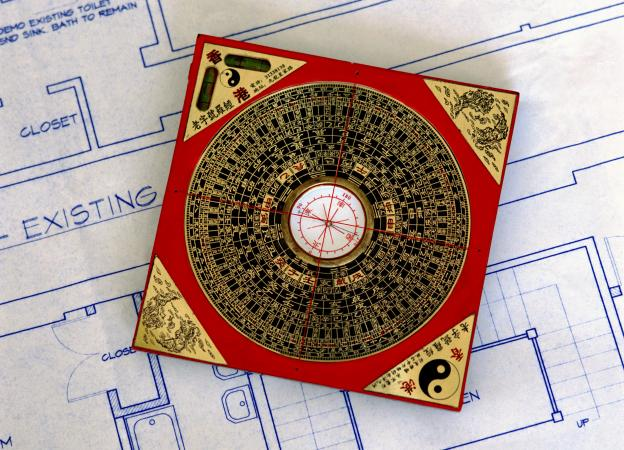 feng shui compass sitting on blueprints