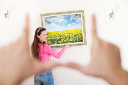 Woman hanging art on wall