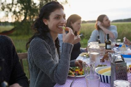 Smiling woman eating with friends