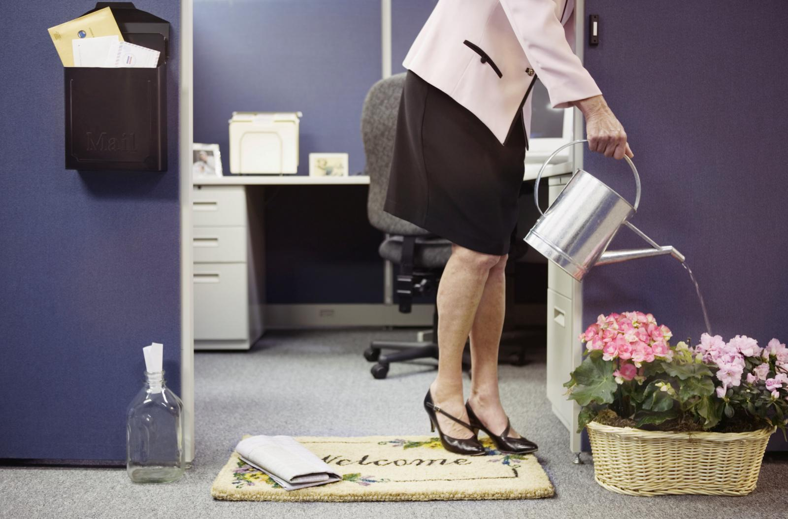 Businesswoman by furnished cubicle