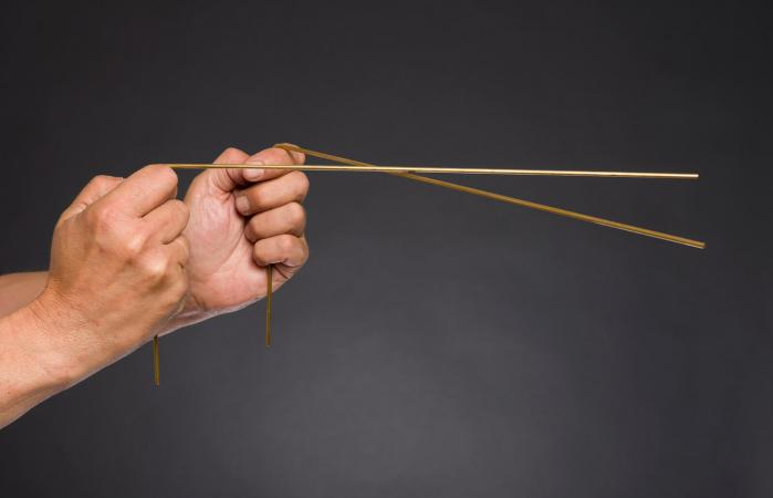 Hands holding a pair of golden dowsing rods