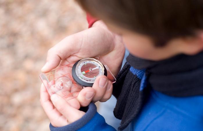 Boy reading a compass
