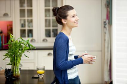 Young woman eating breakfast in her kitchen