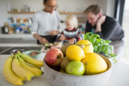 Fruit bowl with fresh fruit and family cooking