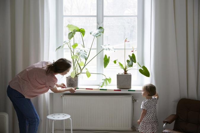 woman and child measuring a window