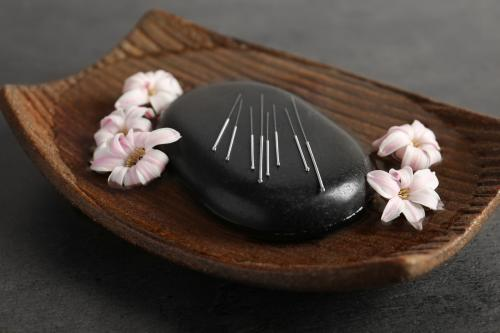 Acupuncture needles on a spa stone