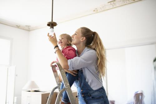 Mother and daughter changing lightbulb