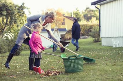 Mother and daughter raking autumn leaves at yard