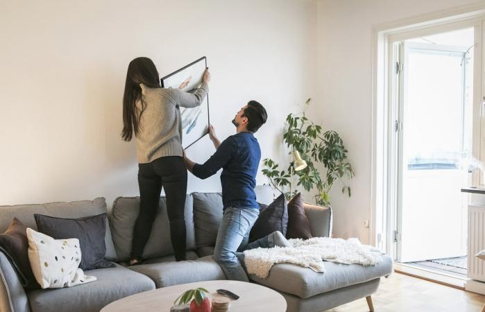 Couple adjusting painting on wall