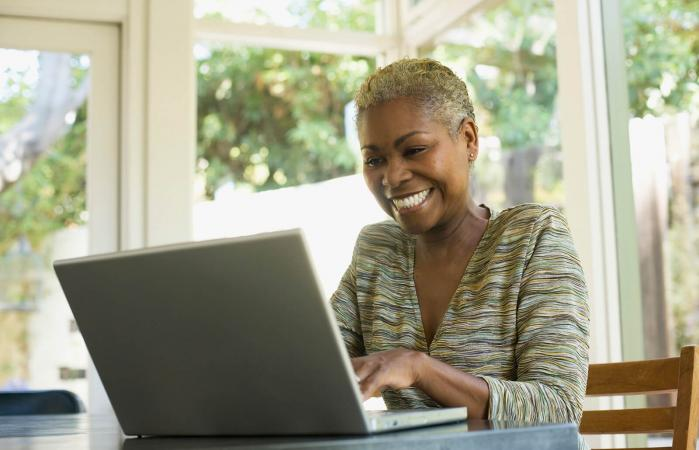 Woman on laptop at a table smiling