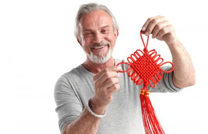 The old man holds the Chinese knot
