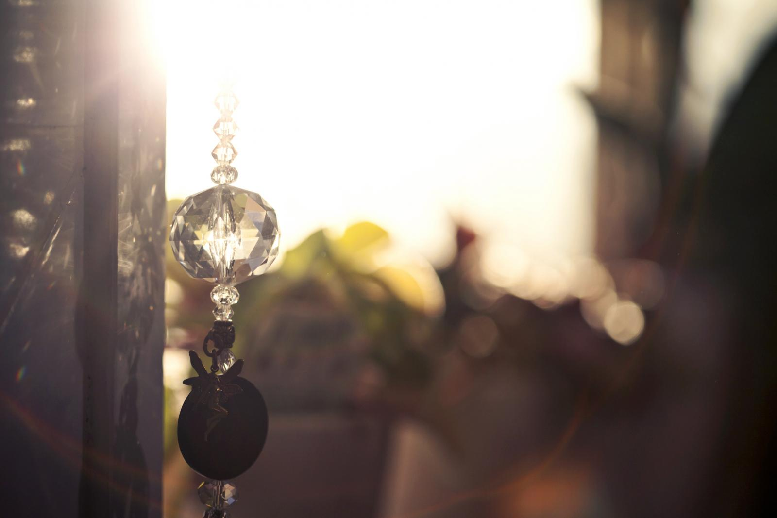 Glass sun catcher hanging next to a window glowing with early morning light