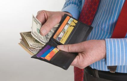 Man with wallet full of dollars