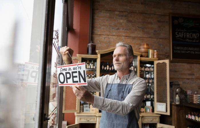Male shop owner hanging open sign