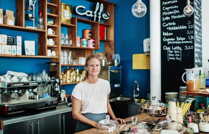 Waitress Standing At Her Coffee Shop Counter