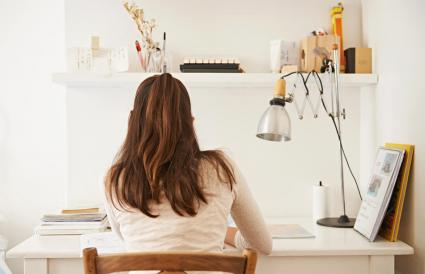 woman studying at her desk at home