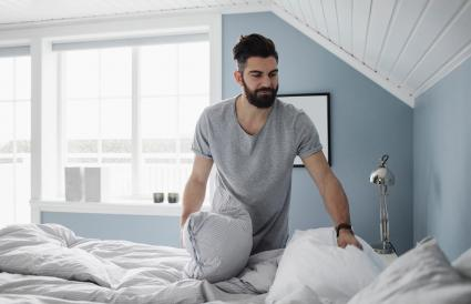 man preparing bed at home