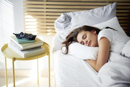 Woman sleeping in bed by daylight