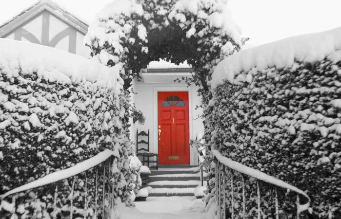 snowy view of house with red door