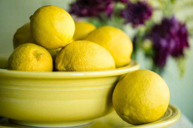 Lemons In Bowl On Plate With Flowers Behind