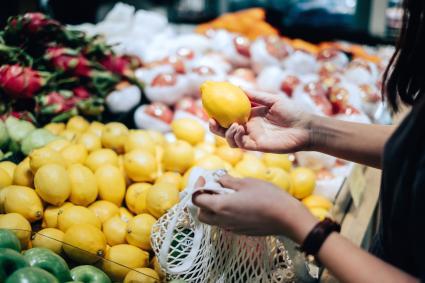 Woman shopping for fresh lemons