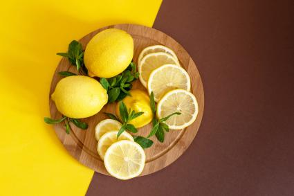 Board with cut lemons and zest on wooden table