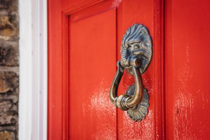 Lion's Head Door Knocker On A Bright Red Door