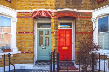 Red and green doors on a brick facade