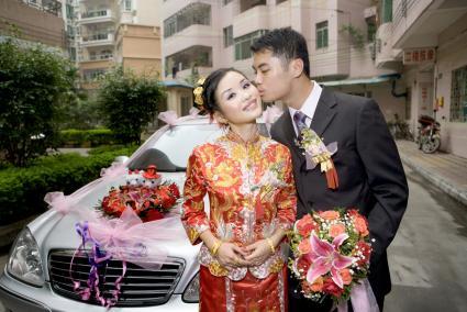 Groom kissing bride on cheek in front of car