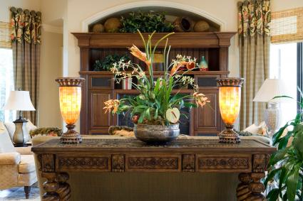 Beautiful carved console table with silk plant and lighted fixtures in a den